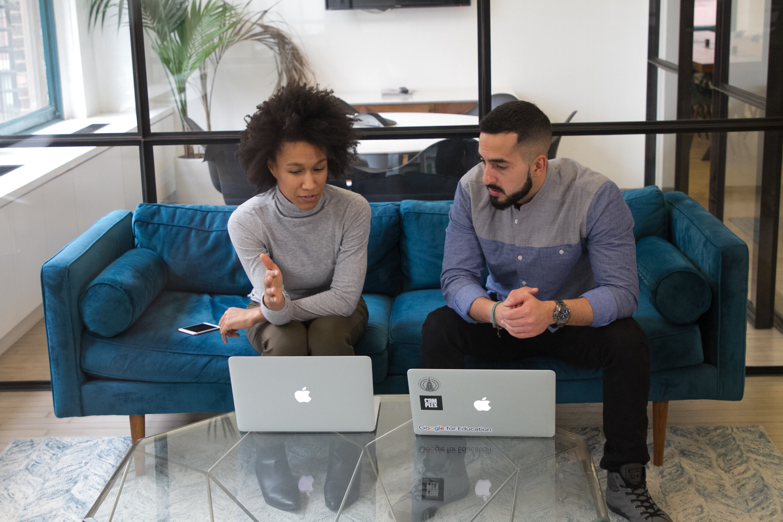 Woman and man sitting on couch looking at laptops