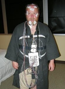 Man with monitoring wires attached for PSG sleep study